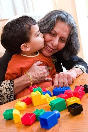 子供のキスを果たしている彼のおもちゃで遊んでいる間彼の祖母 写真素材