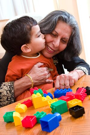 A child plays kisses his grandmother while playing with his toys photo