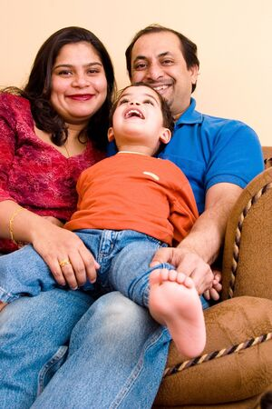 An East-Indian couple site in their living room with their son Stock Photo - 1180431