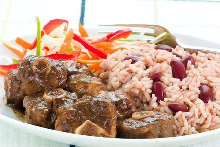 Caribbean style curried Oxtail served with rice mixed with red kidney beans. Dish accompanied with vegetable salad. Shallow DOF. 版權商用圖片