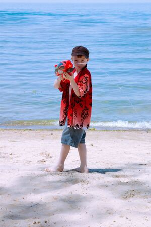 A boy on the beach with his water gun Stock fotó