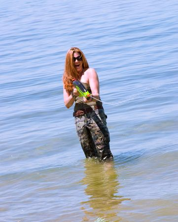 water gun: A woman playing with a water gun on the beach