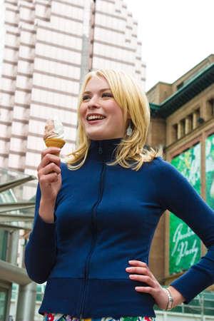 A young woman enjoying an ice cream downtown photo