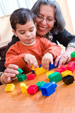 helps: A child plays with his blocks while his grandmother helps him
