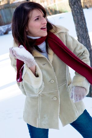 A playful young woman in a snowball fight photo