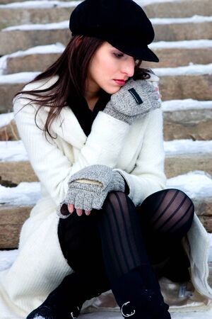 A woman lost in her thoughts sits on the snowed over steps photo