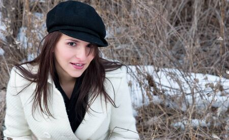 A playful young woman outdoors in the woods on a cold winter day photo