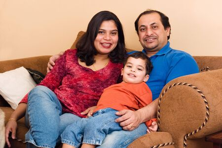 An East-Indian couple site in their living room with their son