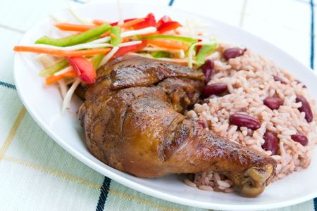 Caribbean style jerk chicken served with rice mixed with red kidney beans. Dish accompanied with vegetable salad. photo