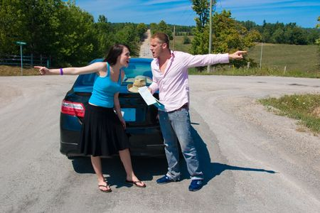 A young couple at a crossroad argue on which way to go Stock Photo