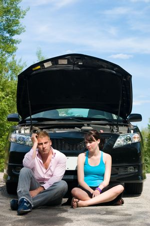 roadside assistance: A young couple sits dejectedly as their car breaks down
