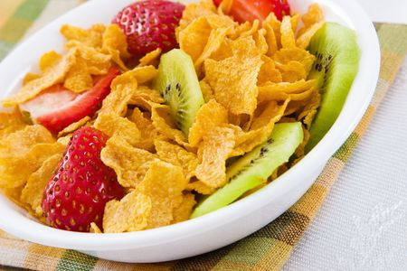 Delicious bowl of corn flakes with strawberries and kiwi fruit.