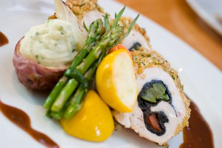 enticing: Breaded chicken slices stuffed with sweet peppers and served with asparagus and vegetables Stock Photo