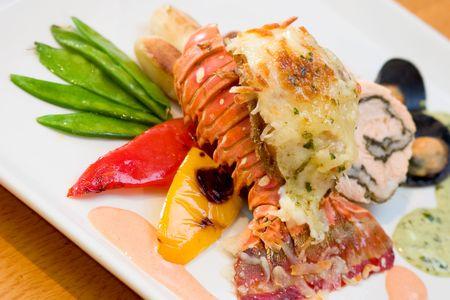 highend: Delizioso pasto di aragosta e pollo ripieno servito con piselli dolci, patate, peperoni e ostriche.