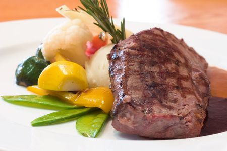 Juicy platter of beef steak served with mashed potatoes, carrots, beans and zucchini. Served with an assortment of sauces. Stock Photo