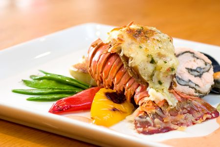 highend: Delicious meal of lobster and stuffed chicken served with sweet peas, potatoes, peppers and oysters.
