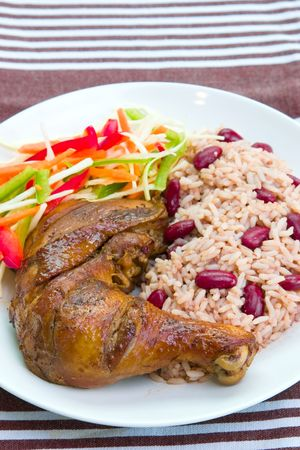 enticing: Caribbean style jerk chicken served with rice mixed with red kidney beans. Dish accompanied with vegetable salad. Shallow DOF. Stock Photo