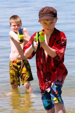 Dos niños juegan en la playa con sus pistolas de agua  Foto de archivo - 2914791
