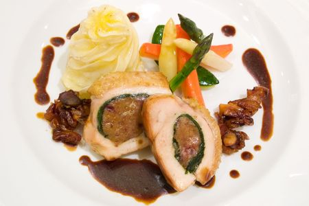 Chicken supreme stuffed with blanched spinach and mince beef. Served with carrots, beans and asparagus. photo