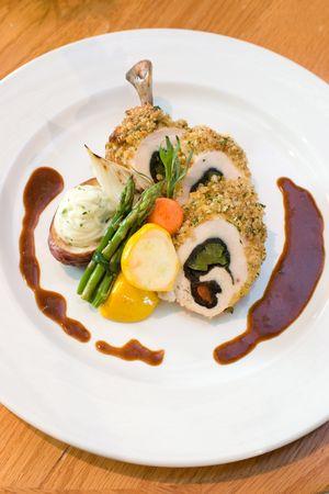 highend: Fettine di pollo impanati ripieni di peperoni dolci e servita con asparagi e verdure. Drizzled con aceto balsamico.