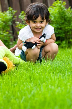 A little girl plays with her toys in the backyard Stock Photo