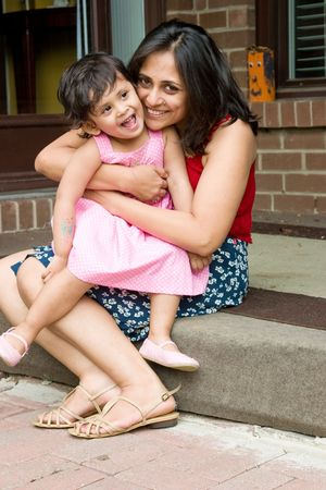 A mother plays with her daughter at the doorstep of the house