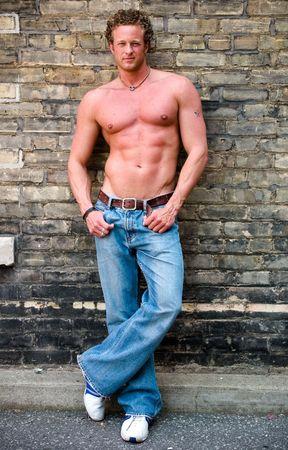 A well built, muscular man stands next to a wall