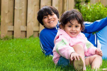 彼の妹、家の裏庭に座っている少年