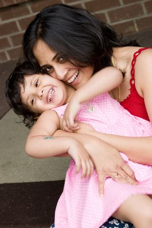 A mother plays with her daughter at the doorstep of the house photo