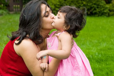 A mother plays kisses her daughter in the backyard Stock Photo
