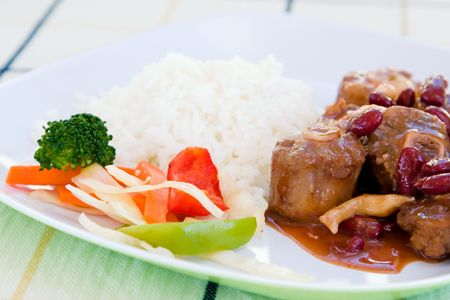 Caribbean style curried Oxtail stew served with rice mixed with red kidney beans. Dish accompanied with vegetable salad. Shallow DOF. Stock Photo