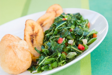 jamaican food: Speciality caribbean dish of callaloo (spinach) served with fried dumplings