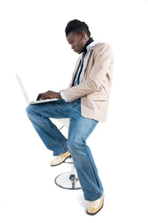 stool: A young african-american man works on the laptop computer