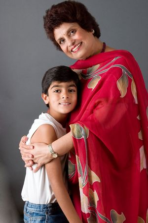 A child with his grandmother against a gray background Stock Photo