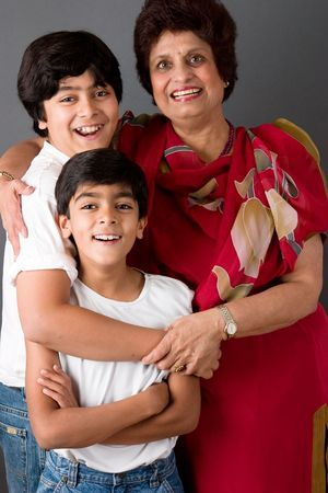 Two children hugging their grandmother against a gray background Stock Photo