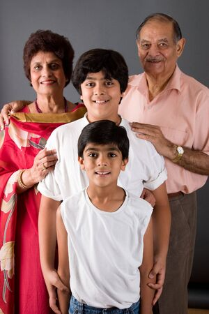 Two children with their grandparents against a gray background Stock Photo
