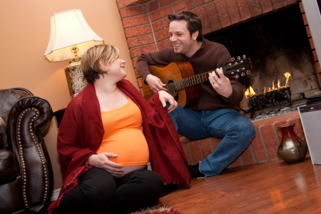 A happy father plays the guitar for his pregnant wife photo