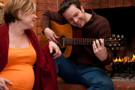 A happy father plays the guitar for his pregnant wife Stock Photo - 4940351