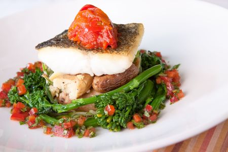 Delectable Atlantic Cod served with fingerling scallion hash, braised rapini, saffron red peppers and bagna cauda sauce Foto de archivo