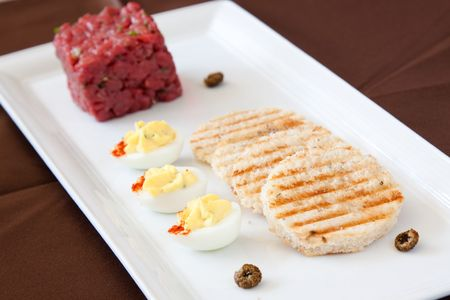 Exotic entree of bison tartare, herbed potato bread, deviled quails eggs, fried ox-eyed capers and chervil essence photo