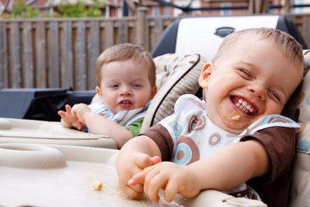 2 つの双子の兄弟のフィード時楽しい時を過します。前に子に焦点を当てます。 写真素材