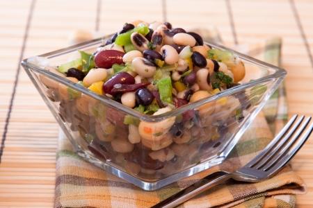 Gezonde salade gemaakt met rode kidney bonen, black eyed peas, mais, lente-uitjes, kikkererwten, selderij en kruiden.