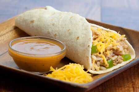 delectable: Delectable tortilla stuffed with rice, chicken, tomatoes, onions, peppers, cheddar cheese, sauce & spices