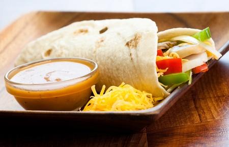 queso cheddar: Deliciosa tortilla rellena con tomates, cebollas, pimientos, champi�ones, queso cheddar, salsa & especias Foto de archivo