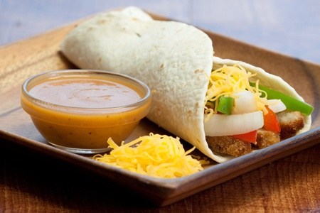 fajita: Delectable tortilla stuffed with chicken, peppers, onions, tomatoes, cheddar cheese, sauce & spices
