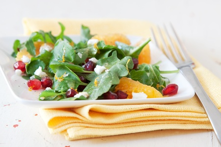 Summer salad of baby spinach, pomegranate and oranges topped with crumbled feta cheese.