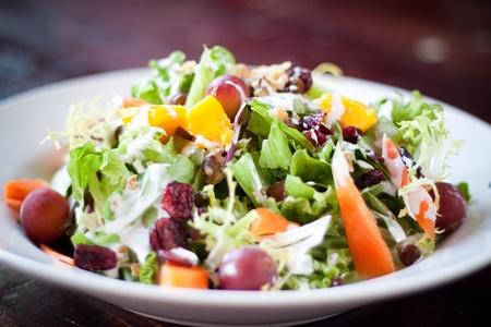 Een heerlijke medley van vers fruit, selderij, wortel en groen overgoten met cranberry's, rozijnen, walnoten en druiven. Gekleed met handtekening mayo, yoghurt en citroen dressing. Focus op de top van de salade.