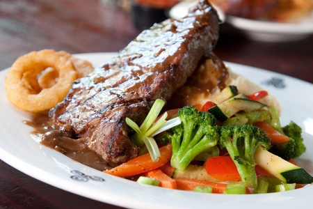 pub food: 10 oz. New York Striploin Angus steak topped with Irish whiskey gravy, saut�ed mushrooms and onion rings. Served with fresh vegetables and mashed potatoes. Goes best with Guinness. Focus on the front of the steak. Stock Photo