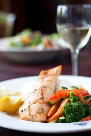 Fillet of salmon baked with our maple glaze, served on a bed of aromatic basmati rice with stir fry vegetables. Pairs perfectly with white wine. Foto de archivo
