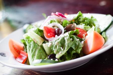 Diverse greens, tomaat, komkommer, zwarte olijven en feta kaas worden gegooid in een traditionele Griekse dressing. Stockfoto